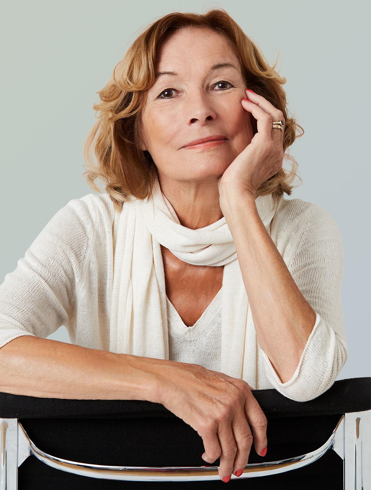 Frau sitzt lässig auf Stuhl und stützt Kopf mit einer Hand ab