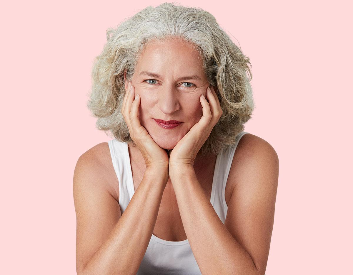 Hübsche, ältere Frau stützt Gesicht auf die Hände und lächelt in Kamera