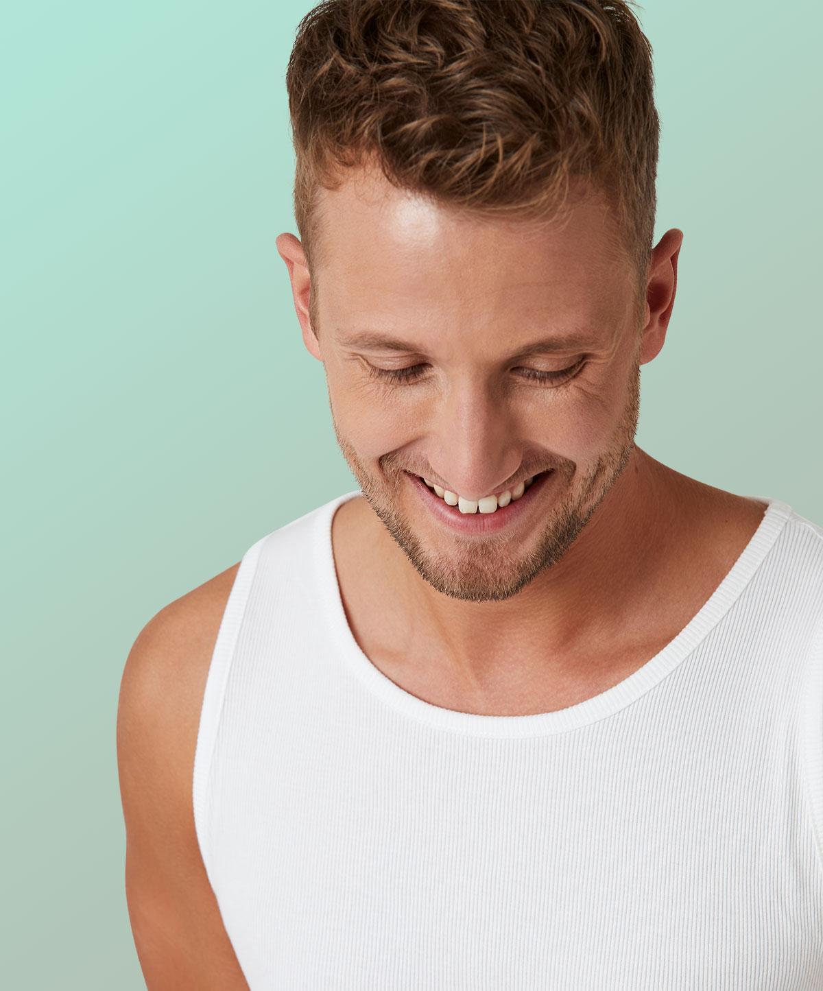 Hübscher Mann lächelt und schaut auf den Boden
