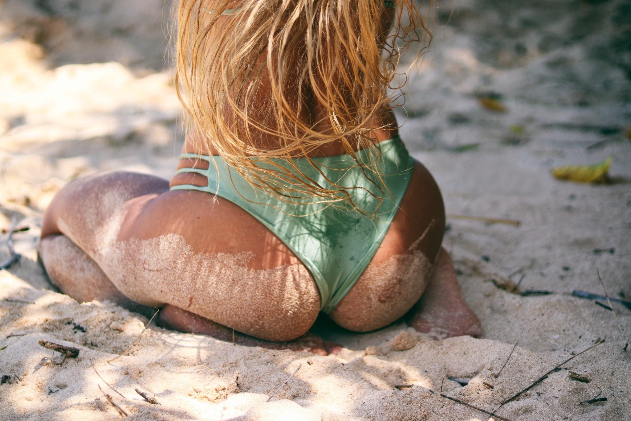 Gesäss von Frau, die am Strand sitzt